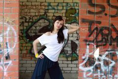 Young  girl near the walls with graffiti Stock Photo
