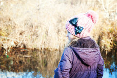 Young girl  near water in the cold season. Back view Stock Images