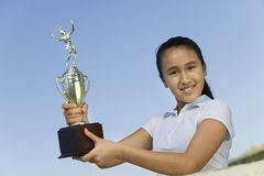 Young girl at net on tennis court holding trophy portrait low angle view Royalty Free Stock Image