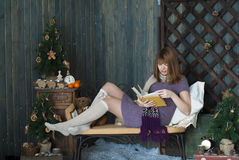 Young girl in a New Year's interior reading a book Royalty Free Stock Images
