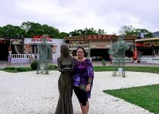 A YOUNG GIRL NEXT TO A STATUE OF A GIRL stock photo