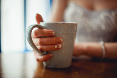Young girl with nice hands with white French manicure holding a blue vintage cup of coffee. Under brown table. selective focus Royalty Free Stock Images