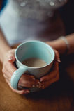 Young girl with nice hands with white French manicure holding a blue vintage cup of coffee. Under brown table. selective focus Stock Photo