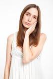 Young girl in nightwear touching her cheek Stock Image