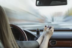 a young girl is not driving safely. Paints toenails while driving. The concept of accidents, inattention at the wheel, the danger royalty free stock photos