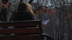 Young girl with notebook relaxing on bench in park. Young girl sits on bench in park and writes in her notebook. Pretty female is relaxing alone on the nature stock footage