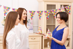 Young girl offering party hats for her friends Royalty Free Stock Photos
