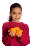 A young girl offering viewer with 3 oranges. Isolated on white background Stock Photos