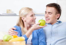 Young girl offers an apple to her husband Stock Photos
