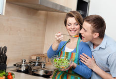 Young girl offers her husband to taste salad Royalty Free Stock Images
