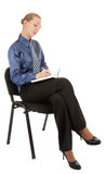 Young girl in the office clothes sitting on a blac. K chair and writes in a notebook on white background royalty free stock images
