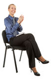 Young girl in the office clothes sitting on a blac. K chair and writes in a notebook on white background stock image