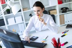 A young girl in the office holds a pen in her mouth and works with a calculator, documents and a computer. Beautiful young girl in a white blouse and black Royalty Free Stock Photos