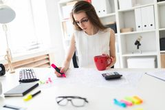 A young girl in the office holds a pink marker, a red mug and works with documents. A charming young girl in glasses and a white blouse is sitting in the office Royalty Free Stock Photography