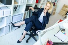 A young girl in the office sits in a chair and throws her legs on the armrest. A slender young girl in a dark suit and in a white blouse is working in the Stock Photo