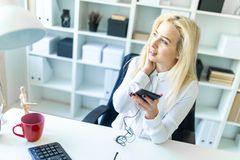 A young girl in the office sits at a desk holding a phone in her hand and talking on it through a headset. A slender young girl in a white blouse is working in Stock Images