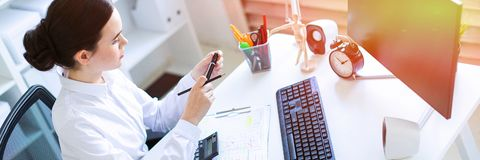 A young girl in the office sits at a table, holds a marker and a pencil in her hand and works with a computer, a. Beautiful young girl in a white blouse and royalty free stock photography