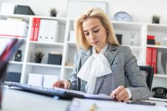 Young girl in office working with computer and documents. A slender young girl in a white blouse, gray jacket and dark trousers is working in the office. The Stock Image