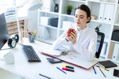 Young girl in the office working with documents and holding an apple. Beautiful young girl in a white blouse and black skirt. Girl with dark hair and beautiful Stock Image