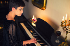 Young girl in old fashioned black dress playing piano drinking wine Stock Photography