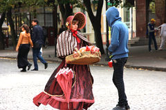 Young girl in old-fashioned dress sells candy from the tray Stock Image