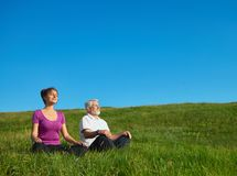Young girl and old man meditating sitting in the field. royalty free stock images