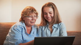 Young Girl and Old Person Learn Laptop Stock Photo