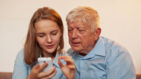 Young Girl and Old Person Learn Smartphone stock footage