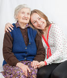 The young girl and the old woman. Old woman and the sweet young girl Stock Photography