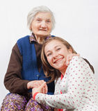 The young girl and the old woman staying together. Old woman and the sweet young girl Stock Image