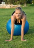 Young Girl On Blue Fitness Ball In The Park Stock Photos