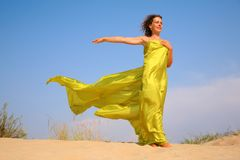 Young Girl On Sand In Yellow Fabric Shawl Royalty Free Stock Photography