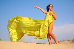 Young Girl On Sand In Yellow Fabric Shawl Royalty Free Stock Photo