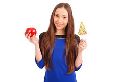Young girl with one lollipop and one apple Stock Images