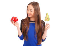 Young girl with one lollipop and one apple Royalty Free Stock Images
