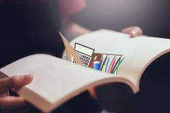 Young girl open the pages of the book empty and a stationary icon. Text for banner lifestyle and school Royalty Free Stock Image