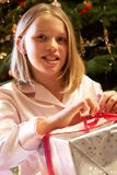 Young Girl Opening Christmas Present. In Front Of Tree Royalty Free Stock Photography