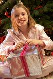 Young Girl Opening Christmas Present. In Front Of Tree Stock Image