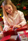 Young Girl Opening Christmas Present. In Front Of Tree Stock Photo