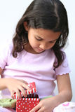 Young Girl Opening Present. Young girl on white background opening a christmas present Royalty Free Stock Images
