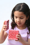 Young Girl Opening Present. Young girl on white background opening a christmas present Royalty Free Stock Photo