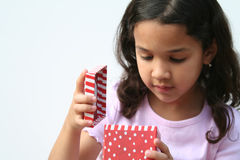 Young Girl Opening Present. Young girl on white background opening a christmas present Royalty Free Stock Photos