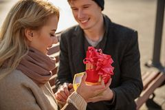 Young girl opening present box and laughing. Lovely couple sitting on bench outdoors. Man is holding hands of women while she is smiling and looking at gift Royalty Free Stock Photos