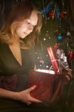 Young girl opening red gift box. Young girl opening x-mass glowing magic present in holiday red gift box with silver ribbons near the Christmas tree. Christmas Royalty Free Stock Image