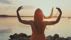 A young girl in an orange dress poses at sunset on the beach and plays with her hair. A young girl in an orange dress poses at sunset on the beach and plays stock video footage