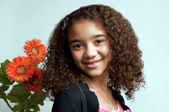 Young girl with orange flower. Young girl with dark complexion and curly hair looking and smiling, standing next to orange flowers, with a white background Royalty Free Stock Photo
