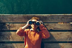 Young Girl Lies On A Pier Near The Sea And Looks Through Binoculars. Travel Search Journey Concept. Young Girl In Orange Jacket Lies On A Pier Near The Sea And Royalty Free Stock Photography