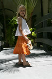 Young girl in orange skirt. A view of a pretty blond girl wearing a white top and orange skirt, standing in the shade on a narrow bridge or walkway Royalty Free Stock Images