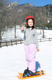Young girl with orange snowshoes and helmet Royalty Free Stock Image
