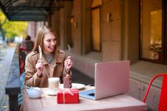 A girl in an outdoor cafe with a laptop talking to someone through a video call, holding cutlery in her hands stock photography